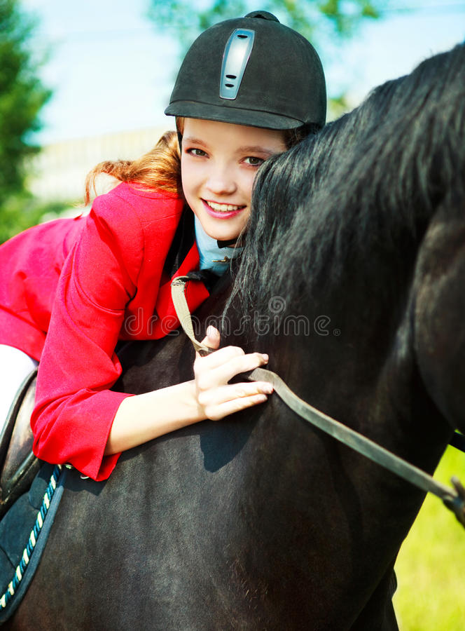 Equestrian. Portrait of a pretty young woman riding a black horse royalty free stock image