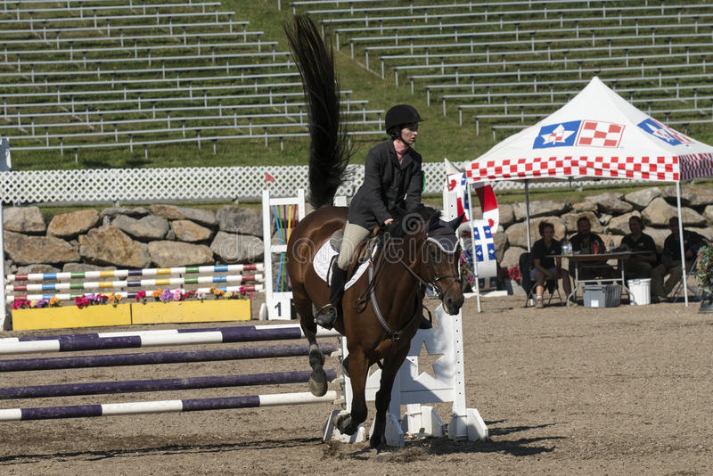 Equestrian. Front view of rider and brown horse completing a jump during competition at the bromont concours June 12, 2016 royalty free stock photography