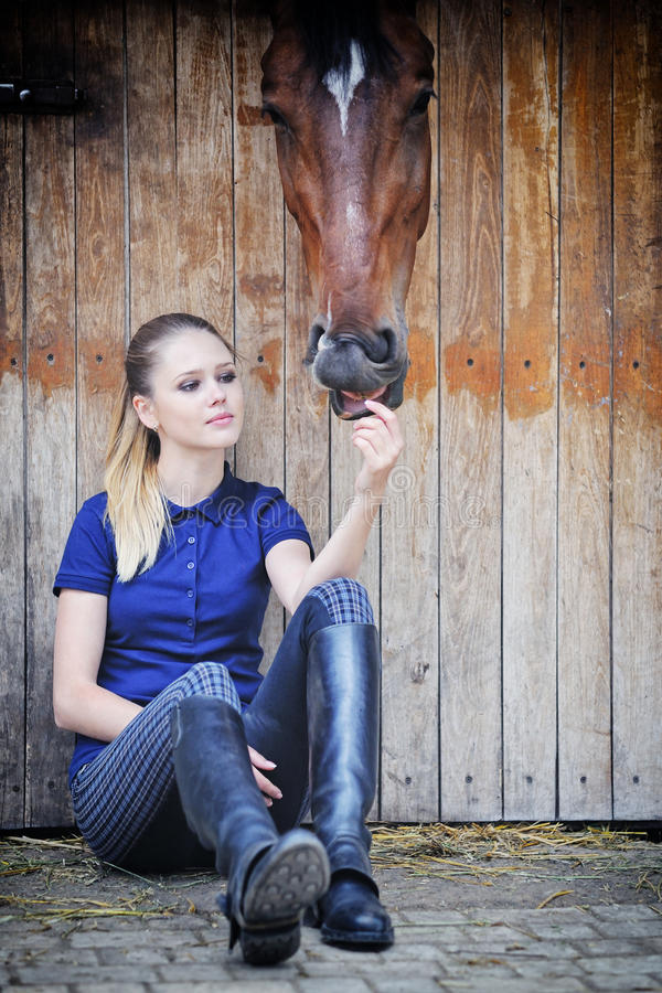 Equestrian girl and horse in stable. Equestrian girl and her horse in stable stock photos