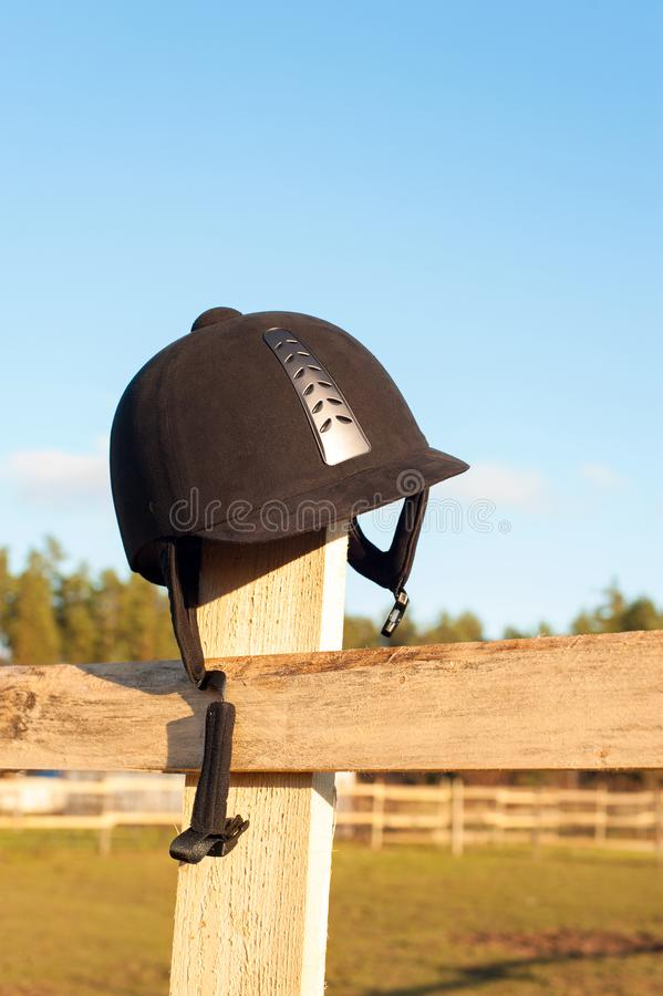 Equestrian helmet forgotten hanging on the wooden fence. stock image