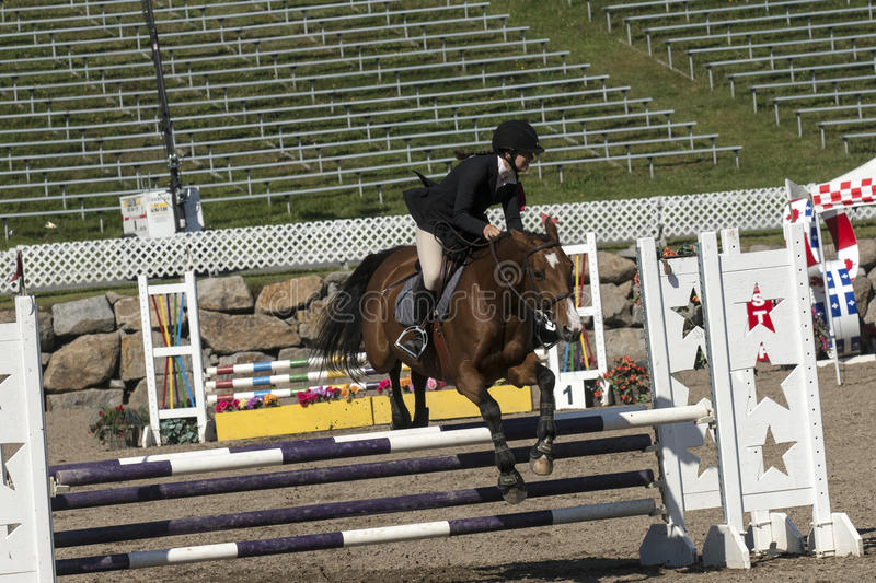 Equestrian - horse jumping. Front side view of rider and brown horse making a jump during competition at the bromont concours June 12, 2016 royalty free stock photos