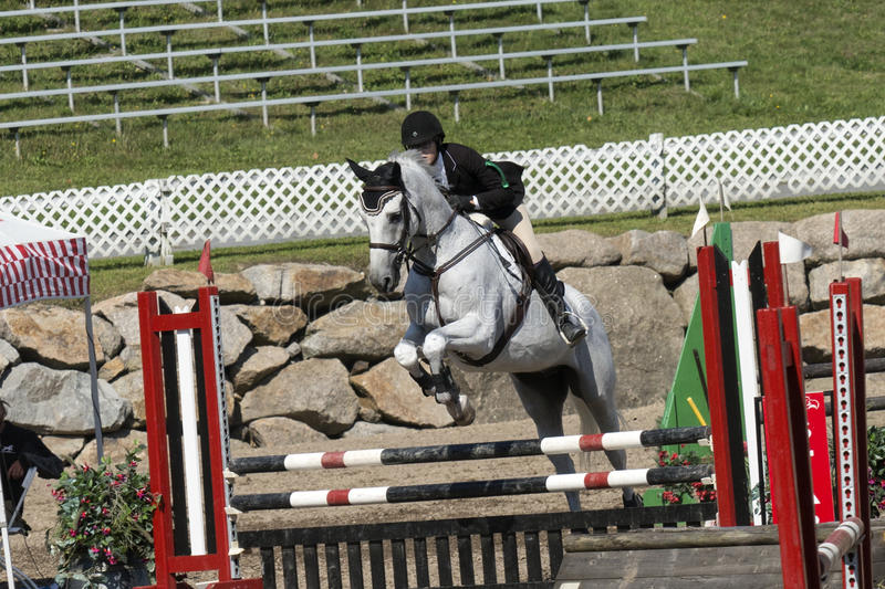 Equestrian - horse jumping. Front side view of rider and white horse making a jump during competition at the bromont concours June 12, 2016 stock photography