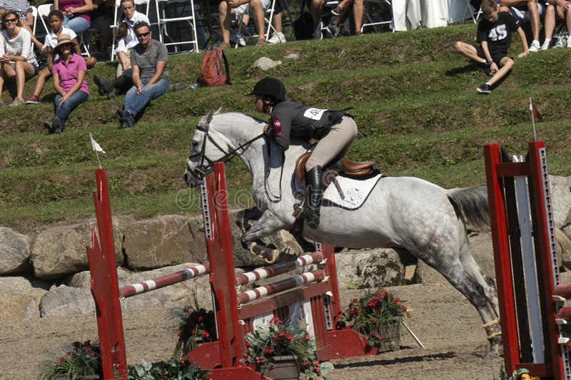 Equestrian - horse jumping. Side view of rider and white horse making a jump during competition at the bromont concours June 12, 2016 stock photography