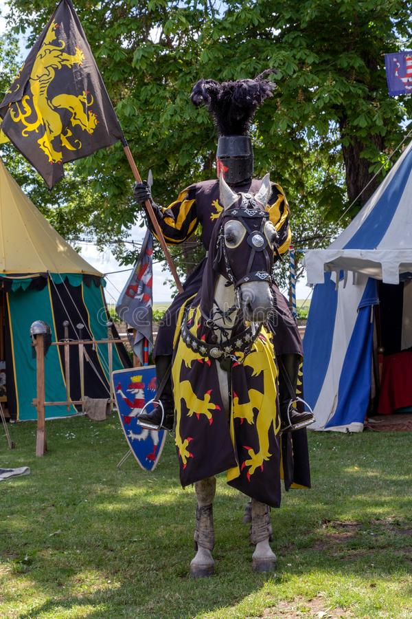 Equestrian knight in armor with a banner. Castle Runneburg, WEISSENSEE, GERMANY - 08.06.2019, knight`s tournament and Pentecost market, equestrian knight in royalty free stock photo