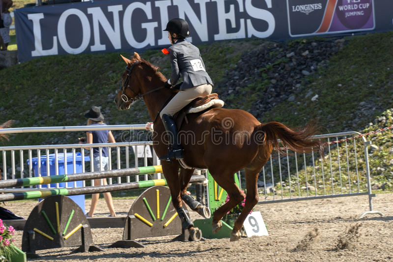 Equestrian. Rear side view of rider and brown horse before the jump during competition at the bromont concours June 12, 2016 stock images