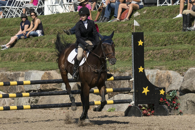 Equestrian show. Front view of young rider completing a jump during competition at the bromont concours June 12, 2016 royalty free stock photo