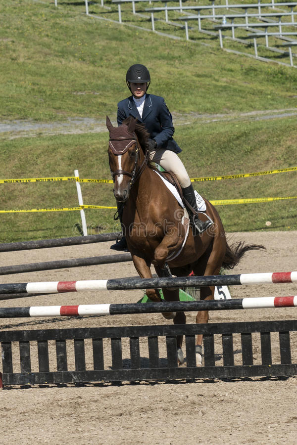 Equestrian show jumping. Front view of rider and brown horse making a jump during competition at the bromont concours June 12, 2016 stock photos