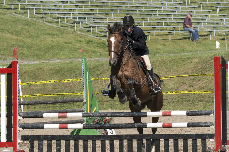 Equestrian show jumping. Front view of young rider and brown horse making a jump during competition at the bromont concours June 12, 2016 royalty free stock images