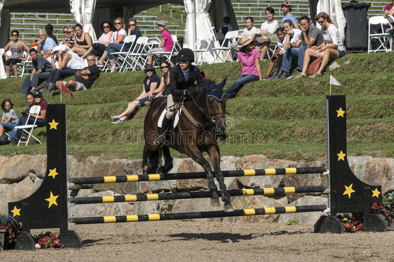 Equestrian show jumping. Picture of horse and rider making a jump during competition at the bromont concours June 12, 2016 stock photography