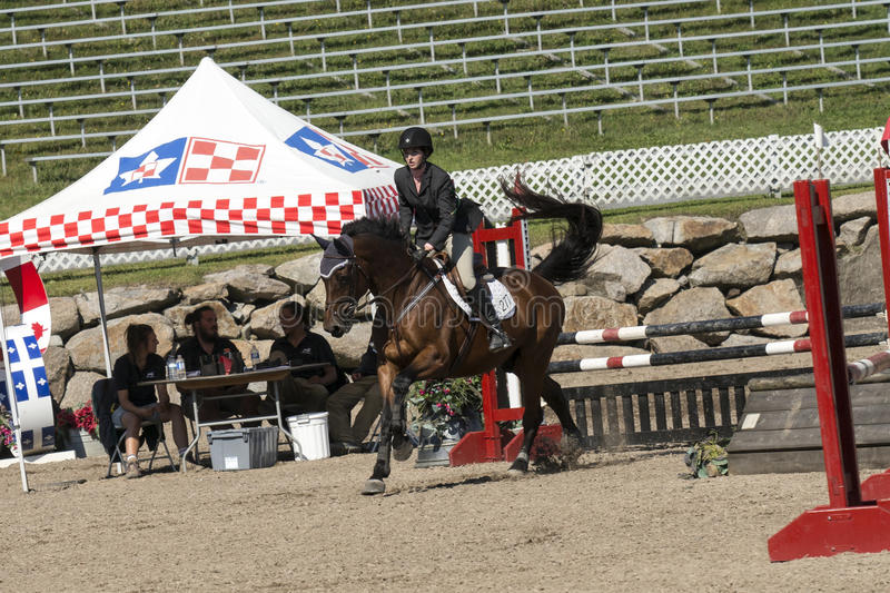 Equestrian show. Picture of rider and brown horse completing a jump during competition at the bromont concours June 12, 2016 royalty free stock images