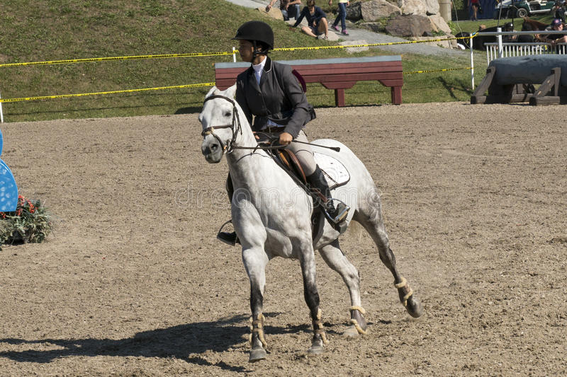 Equestrian show. Picture of rider and white horse riding during competition at the bromont concours June 12, 2016 stock image