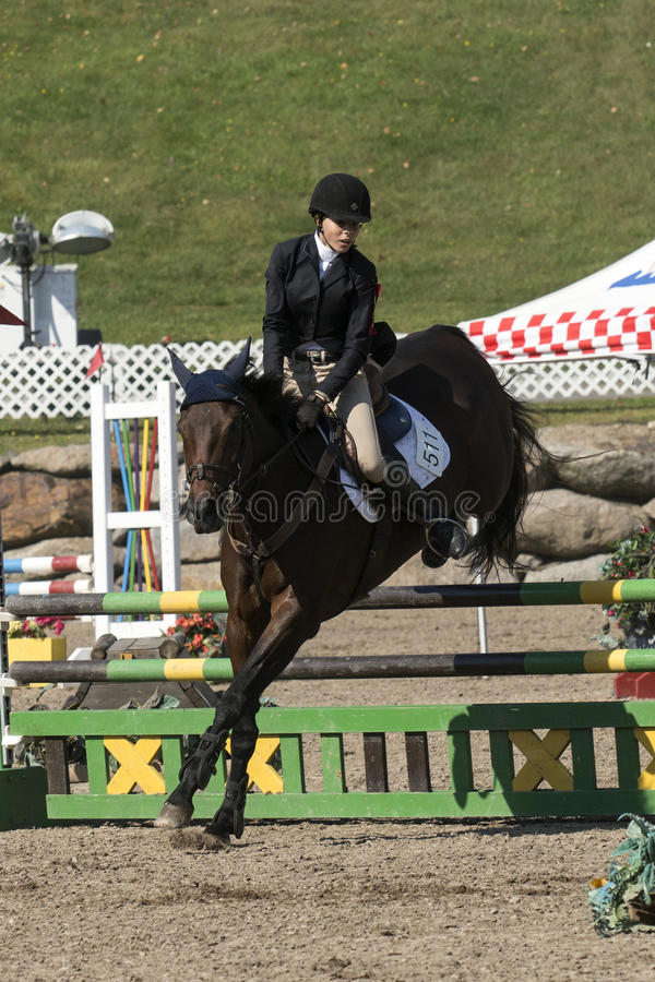 Equestrian sport. Front side view of young rider completing a jump during competition at the bromont concours June 12, 2016 royalty free stock images