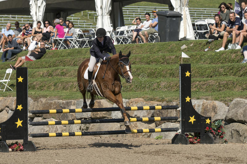 Equestrian sport. A horse rider making a jump with beautiful brown horse at the bromont concours June 12, 2016 stock photos