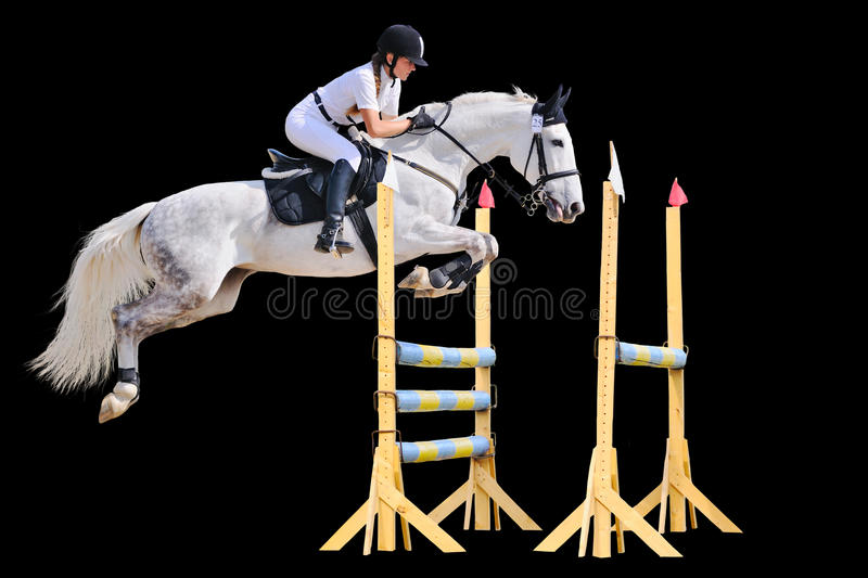 Equestrian sport: young girl in jumping show. (isolated on black royalty free stock image