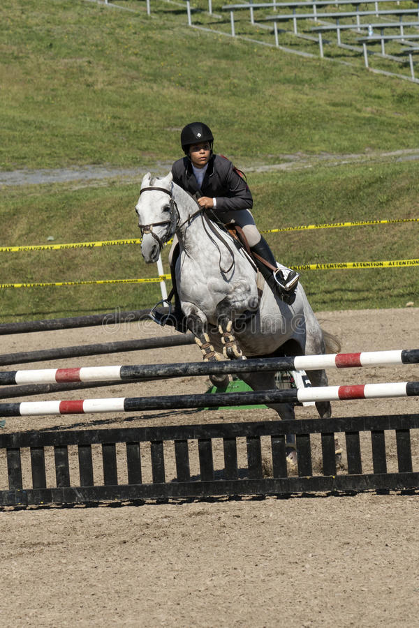 Equestrian sport: young girl in jumping show. Picture of rider and white horse making a jump during competition at the bromont concours June 12, 2016 royalty free stock photo