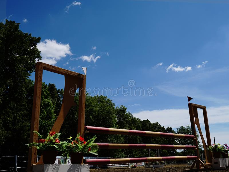 Equestrian sporting competition. Wooden barrier No horse. Against the background of green forest. And blue sky royalty free stock images