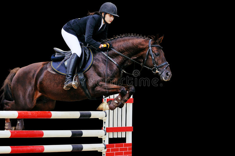 Equestrianism: Young girl in jumping show, isolated on black. Background stock photos