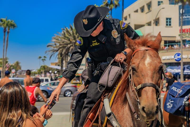 Equestrianska poliser från polisavdelningarna Huntington Beach och Santa Ana framför Huntington Beach Pier arkivfoton