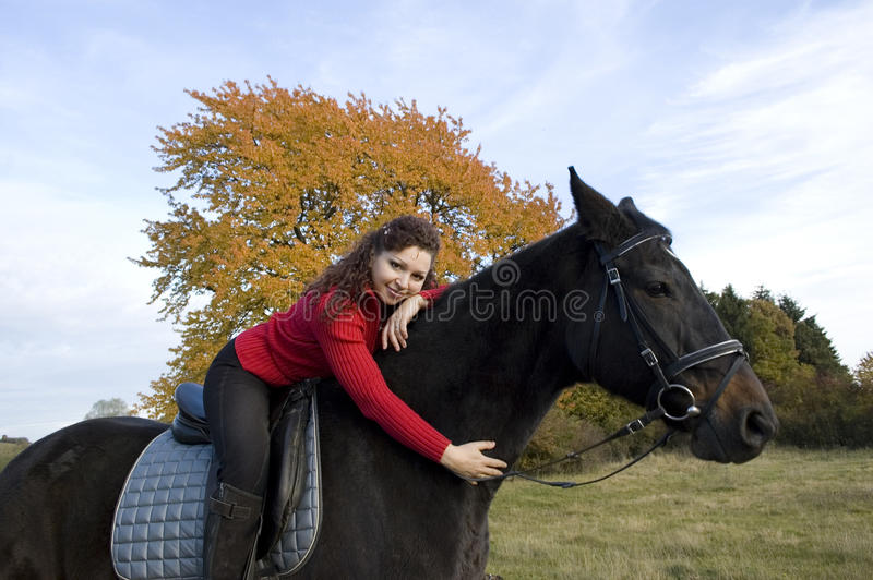 Equestrienne and horse. Horsewoman lay down on the withers of the horse royalty free stock photo