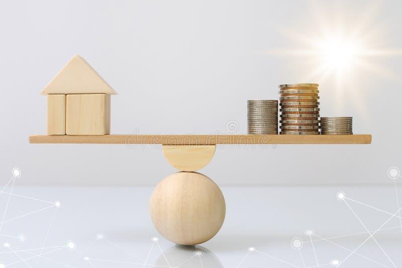 Equilíbrio de madeira da prancha da comparação de madeira do dinheiro da casa e das moedas da despesa do controle da renda com o  imagens de stock royalty free