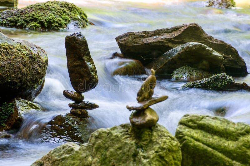 Equilíbrio de pedra pelo rio imagem de stock