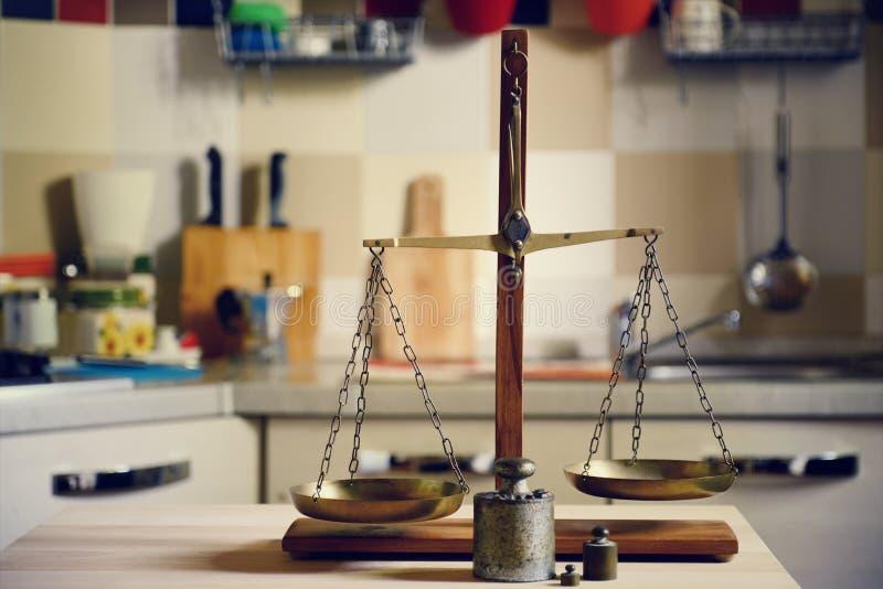Equilíbrio velho na tabela de madeira no fundo da cozinha fotografia de stock