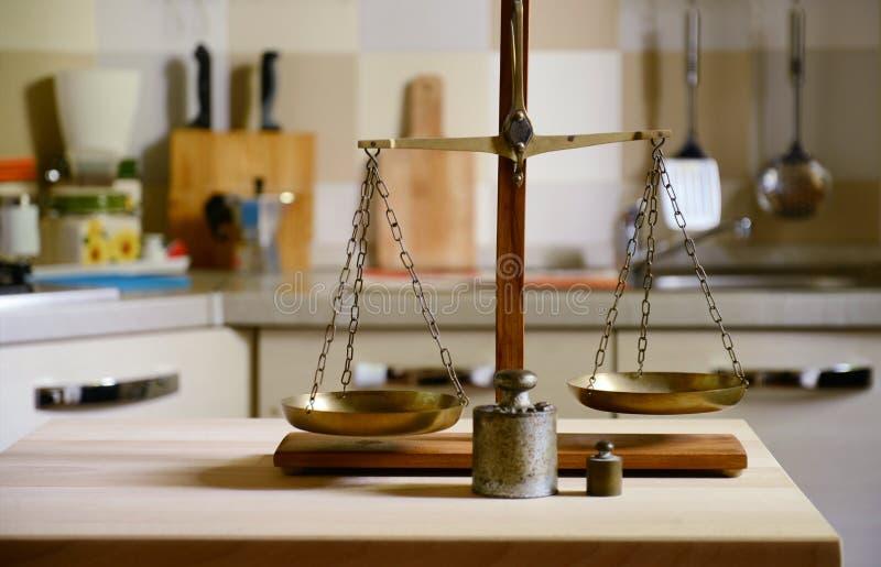 Equilíbrio velho na tabela de madeira no fundo da cozinha fotos de stock royalty free