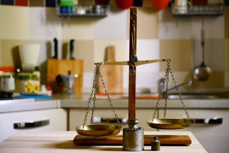 Equilíbrio velho na tabela de madeira no fundo da cozinha fotos de stock