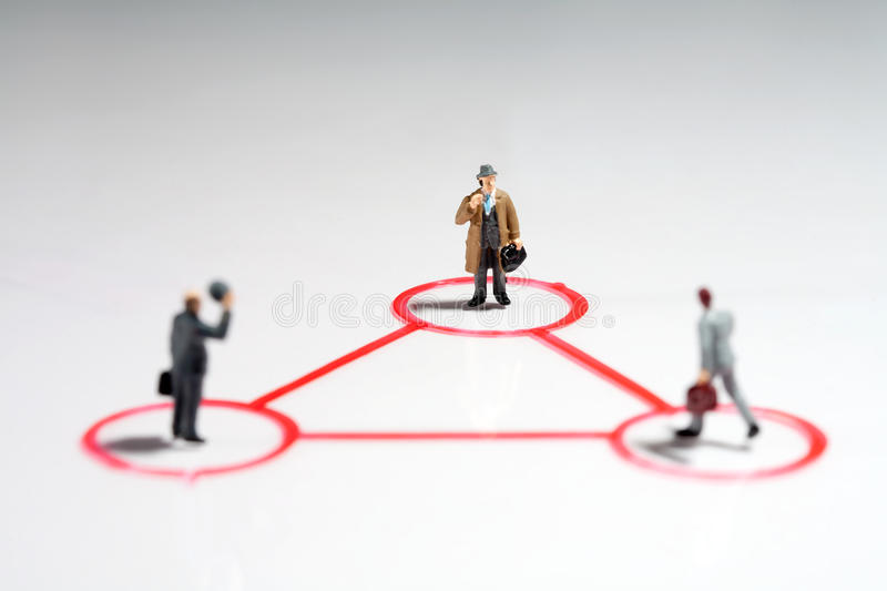 Equilateral triangle of businessmen. Equilateral triangle of tiny miniature businessmen with focus to the man in the rear in a teamwork, leadership and seniority stock image