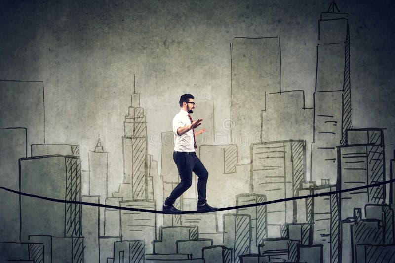 Equilibratura di camminata dell'uomo d'affari su una corda sopra una città fotografia stock libera da diritti