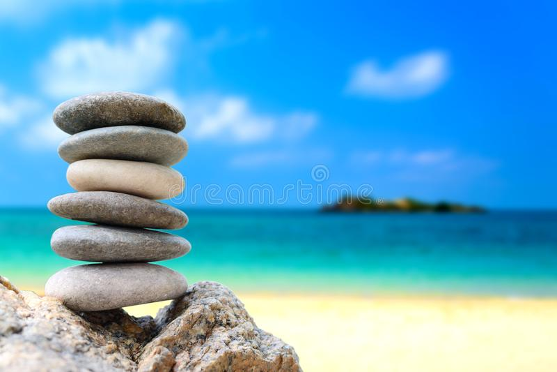Equilibre las piedras con la playa y el mar azul para el concepto del balneario imagenes de archivo
