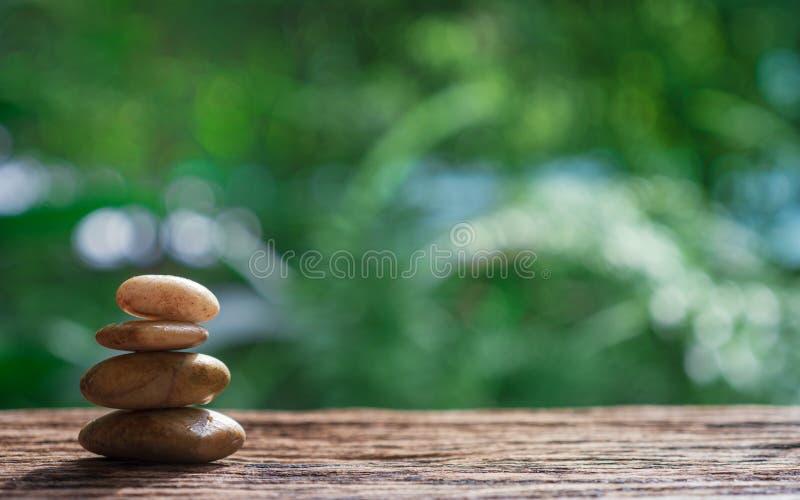 Equilibre los ZENES Stone en la madera con el fondo verde del bokeh de la naturaleza fotos de archivo libres de regalías