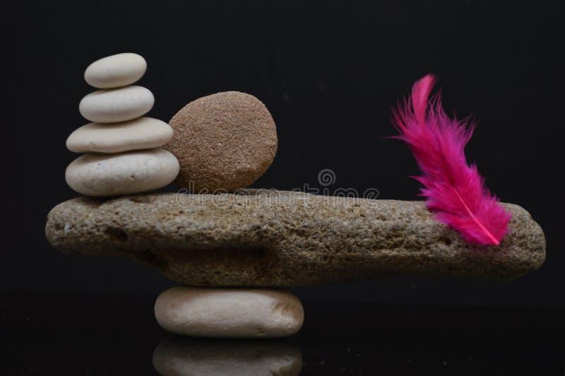 Equilibrio con le pietre e la piuma rossa fotografia stock libera da diritti