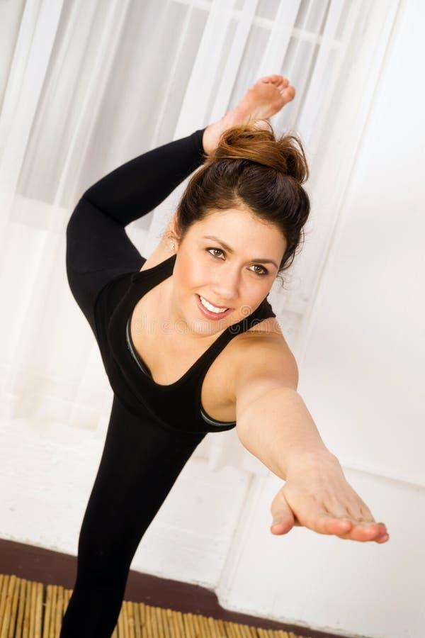Equilibrios atractivos jovenes de la mujer que colocan práctica de la yoga de la actitud foto de archivo