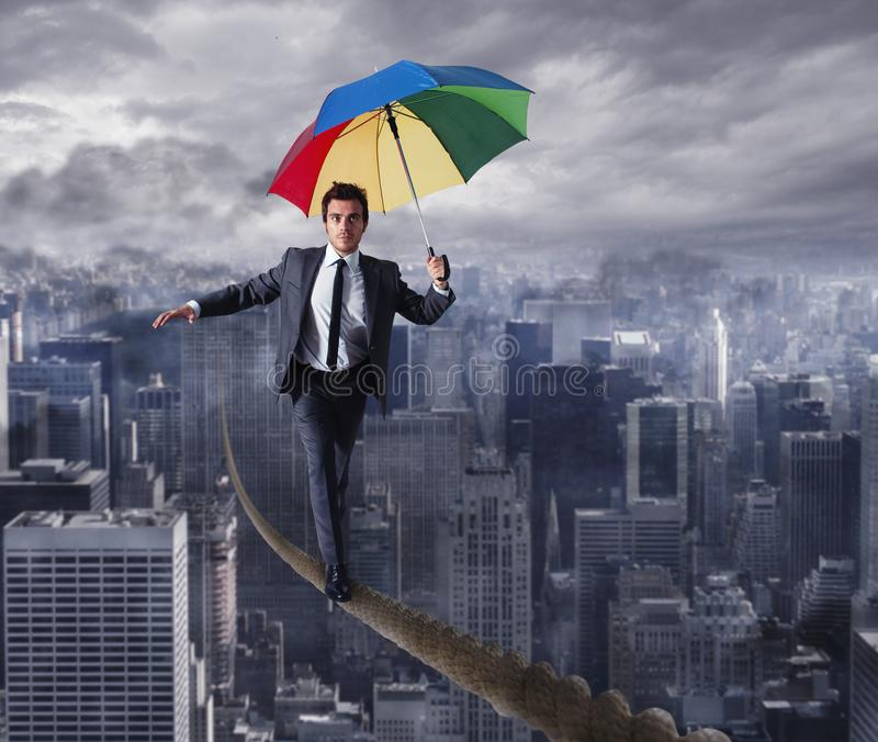 Equilibrist businessman walk on a rope with umbrella over the city. Concept of overcome the problems and positivity. Equilibrist businessman walk on a rope with stock images