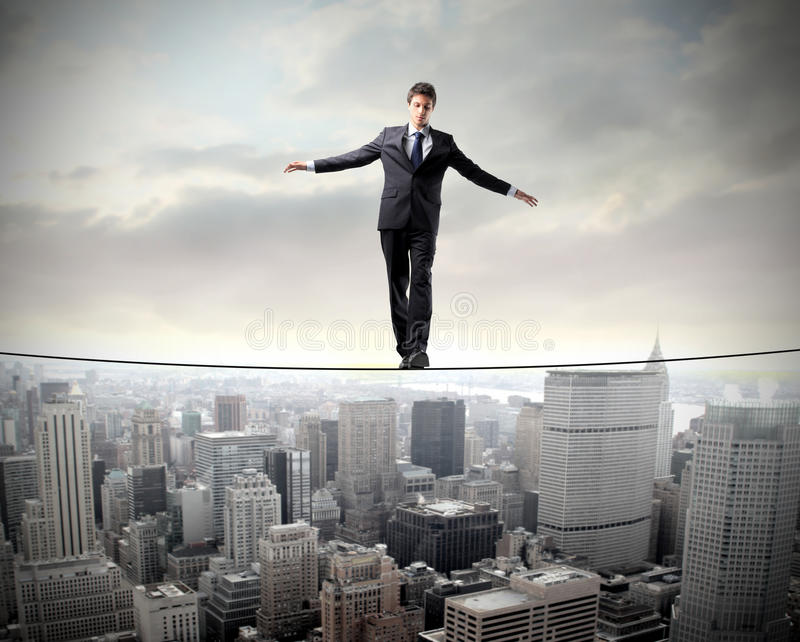 Equilibrium. Businessman standing in equilibrium on a rope over a cityscape stock image