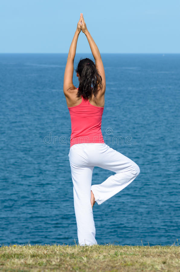 Equilibrium and sea. Woman doing yoga equilibrium and stretchin towards the sea on summer. Tree pose exercise royalty free stock photography