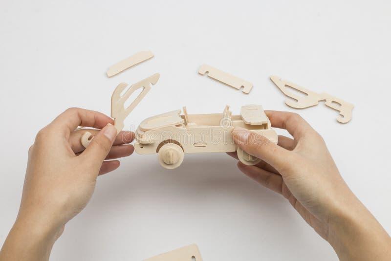 Equipa as mãos que montam o brinquedo de madeira do carro fotografia de stock