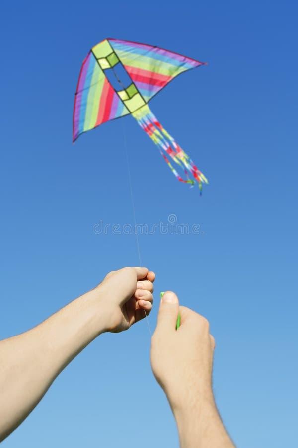Equipa as mãos que voam o papagaio colorido imagens de stock