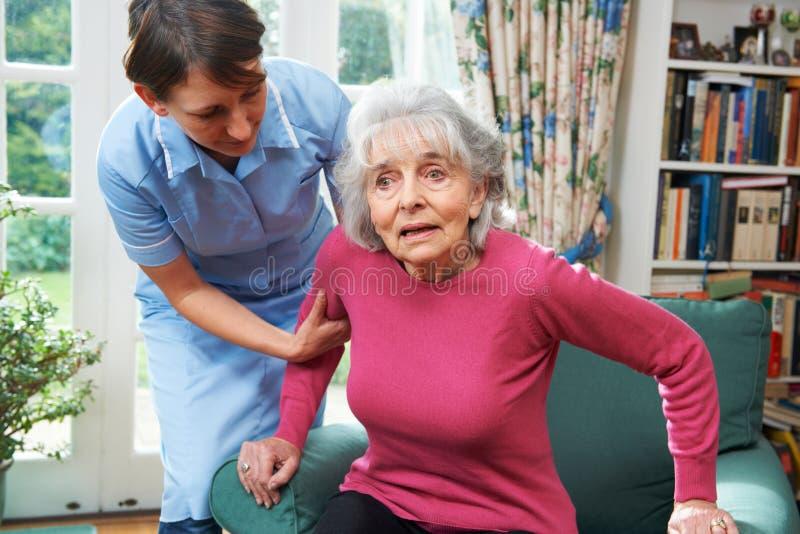 Equipa de tratamento que ajuda a mulher superior fora da cadeira fotos de stock