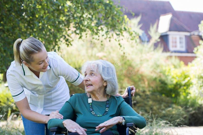 Equipa de tratamento que empurra a mulher superior na cadeira de rodas no jardim fotos de stock royalty free