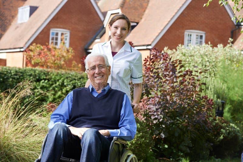 Equipa de tratamento que empurra o homem sênior na cadeira de rodas fotos de stock