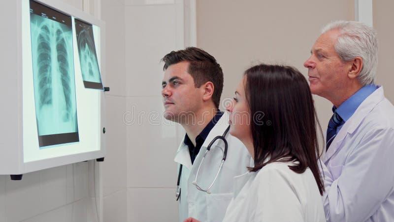 A equipa médica analizes o raio X na caixa de opinião do raio X foto de stock