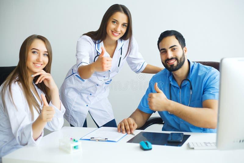 A equipa médica bem sucedida feliz trabalha junto no hospital foto de stock
