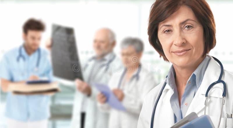 Equipa médica fêmea sênior do doutor no fundo fotografia de stock royalty free