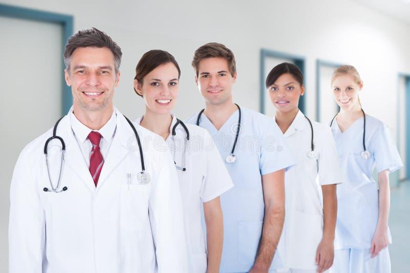 Equipa médica que está na fileira no hospital imagens de stock