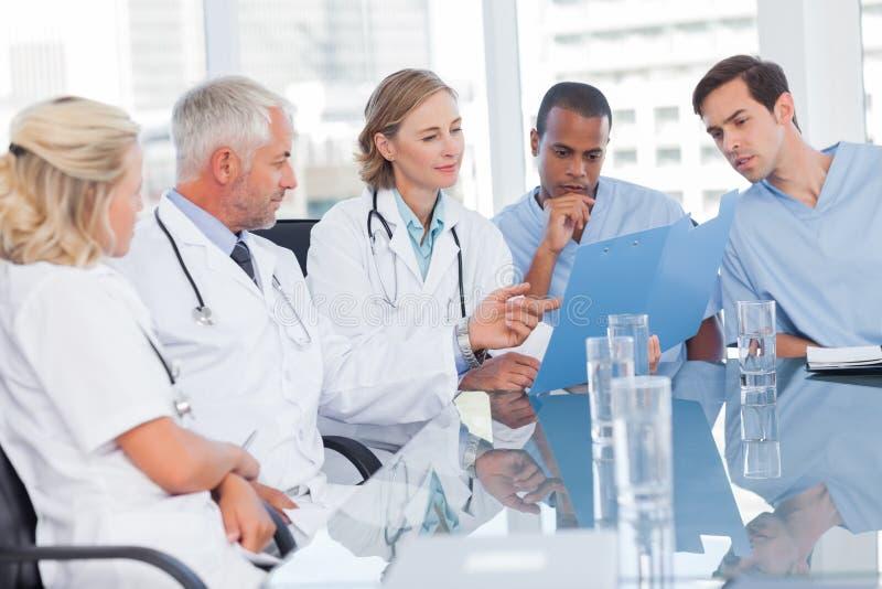 Equipa médica que examina um arquivo foto de stock royalty free