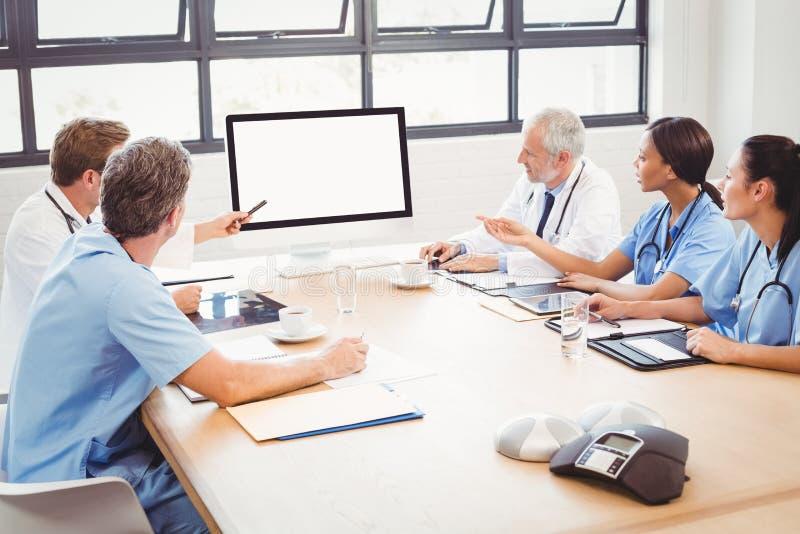 Equipa médica que interage na sala de conferências fotografia de stock