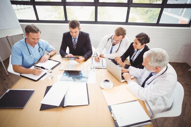 Equipa médica que tem uma reunião na sala de conferências imagens de stock