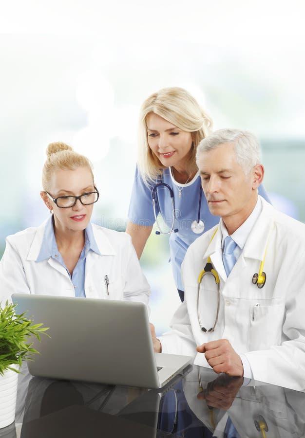 equipa médica que trabalha com portátil imagem de stock royalty free